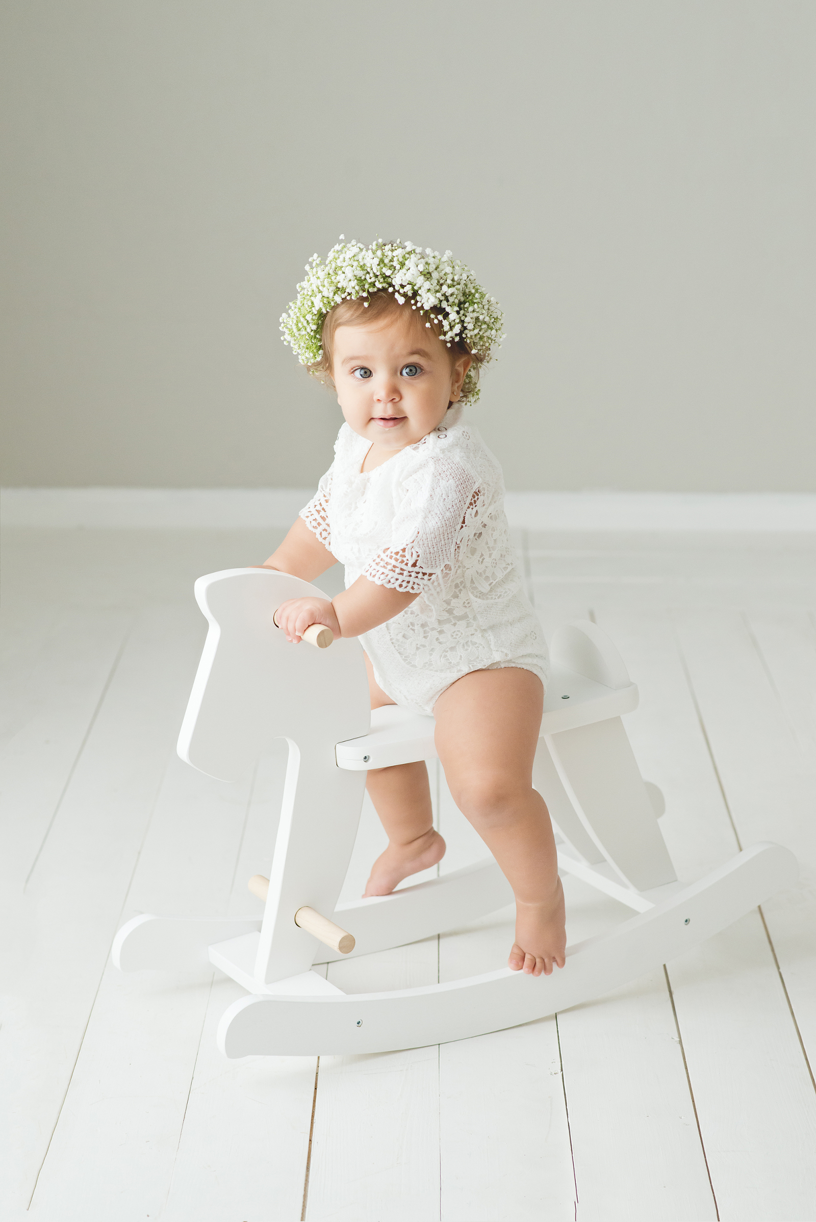 Chandler's baby photographer baby girl on rocking horse baby's breath flower crown