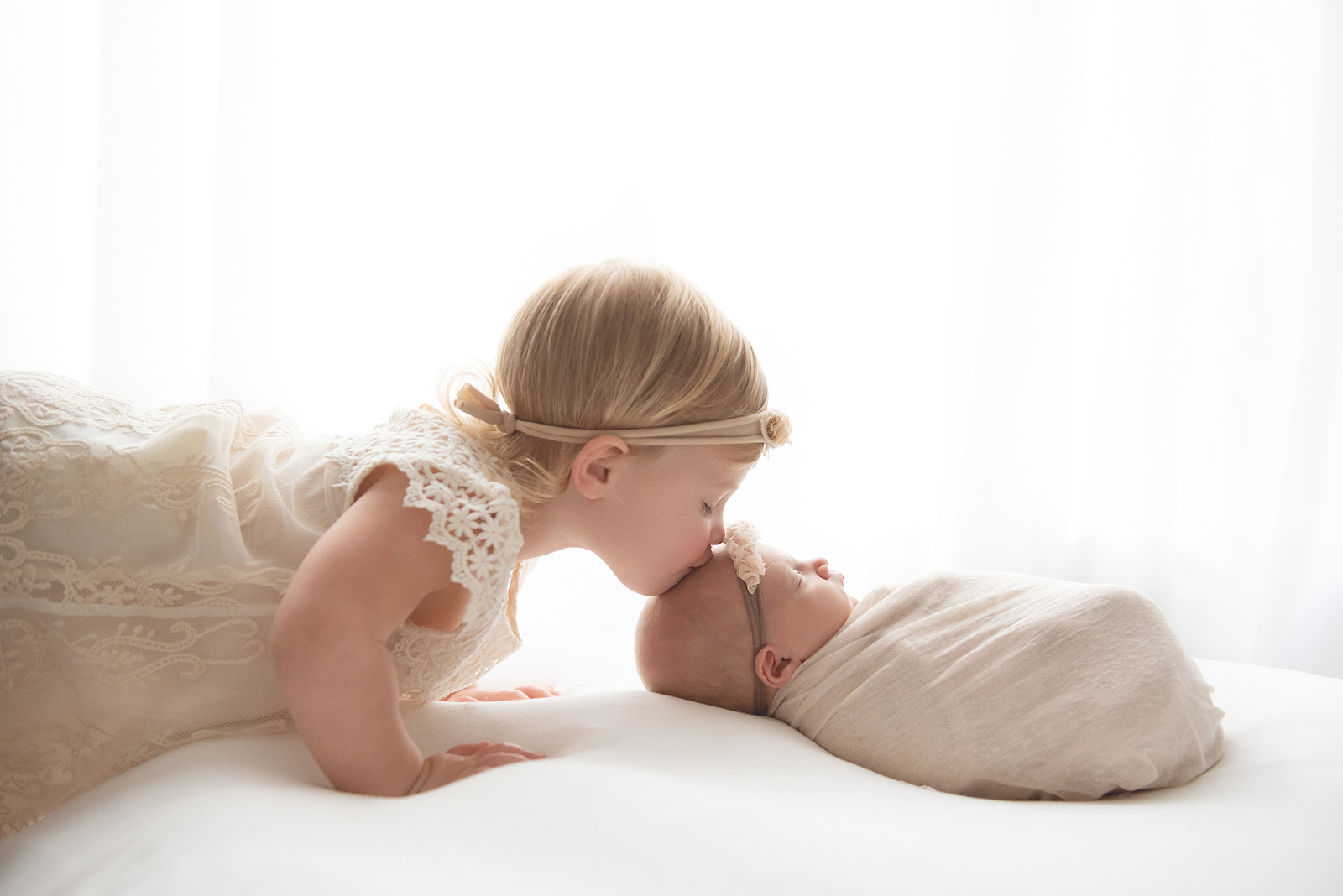 newborn with big sister kissing on head Chandler newborn baby photographer